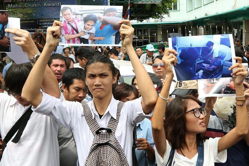 Thai pro-democracy activists demonstrate outside Pathumwan Police Station in Bangkok as they mark the one-year anniversary of Thailand's military coup on May 22, 2015.