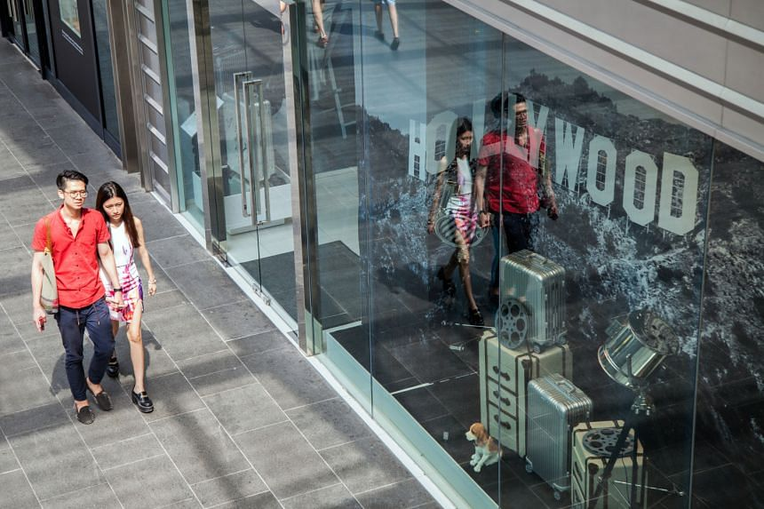 A couple walk past a Rimowa store on Orchard Road in Singapore, on June 21, 2015. Consumer prices prices declined for a sixth straight month in April and employment contracted last quarter for the first time since 2009. PHOTO: BLOOMBERG