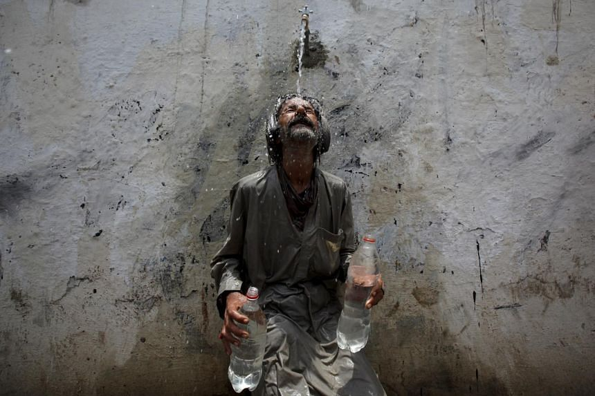 A man cooling off after filling bottles with water at a public tap in Karachi yesterday. The heatwave has led to a surge in power demand, causing blackouts and crippling the water system. -- PHOTO: REUTERS