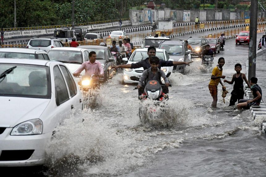 Commuters making their way through a flooded street during heavy rain in Bhopal, India, this week. A new report in The Lancet analyses the health effects of recent episodes of severe weather that scientists have linked to climate change.
