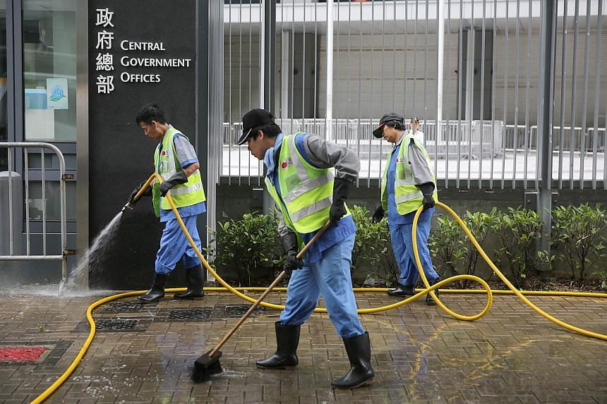 Workers washing the sidewalk after the clearance of the last pro-democracy site in Hong Kong. A ruling from Beijing sparked off the public protests over how Hong Kong chooses its next leader in 2017.