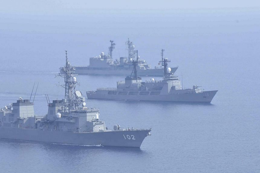 Japanese Maritime Self-Defence Force ships Harusame (foreground) and Amagiri (top) sail together with the Philippine warship BRP Ramon Alcaraz during their joint naval drill in the South China Sea on May 12, 2015.