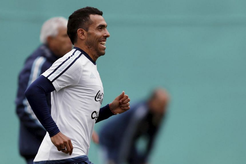Argentina's striker Carlos Tevez smiles as he runs during a training session in La Serena, June 22, 2015. Tevez is set to return to his first club, Boca Juniors.