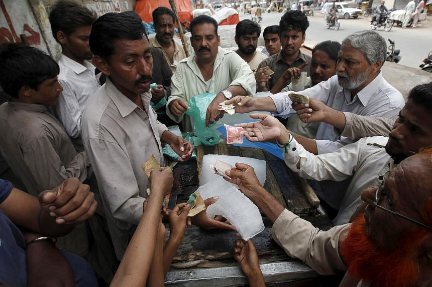 People buy ice blocks from a vendor along a road during a heat wave in Karachi, Pakistan, June 24, 2015.