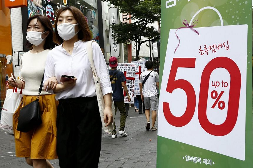 South Korean consumers wearing protective facial masks walk by the sale store on the Myeong-dong street in Seoul, South Korea.