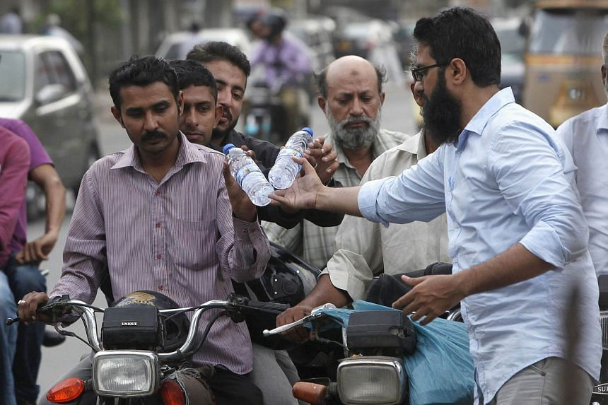 A volunteer distributes water bottles to commuters along a road during the intense hot weather in Karachi, Pakistan on June 24, 2015.