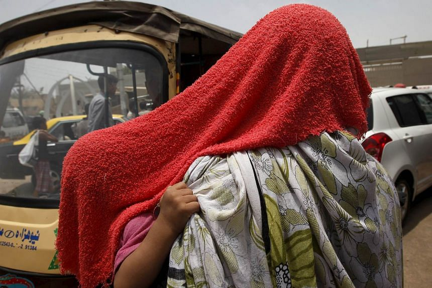 A child grabs her mother's scarf as they are both covered with a water-soaked towel, to beat the heat.