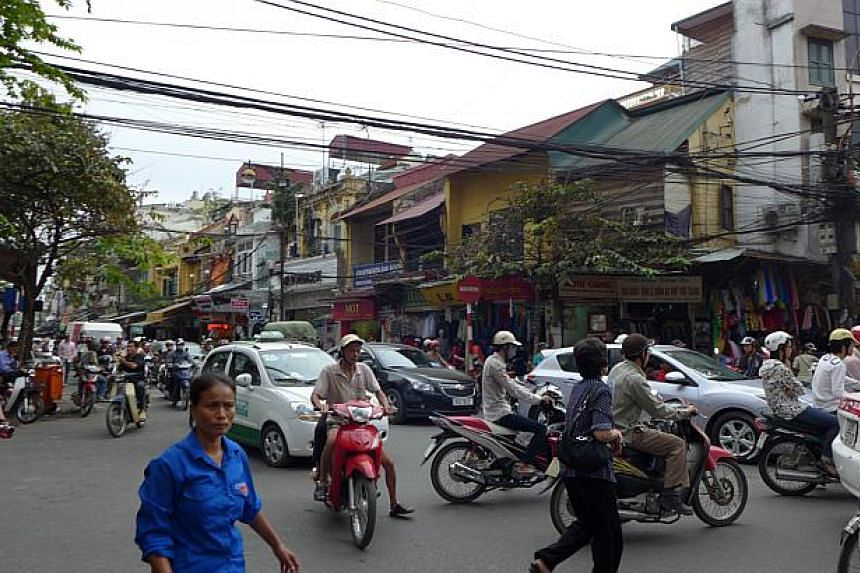 To cross the street in Hanoi's heavy traffic, simply step off the pavement, walk in a confident manner and watch the vehicles slalom around you.