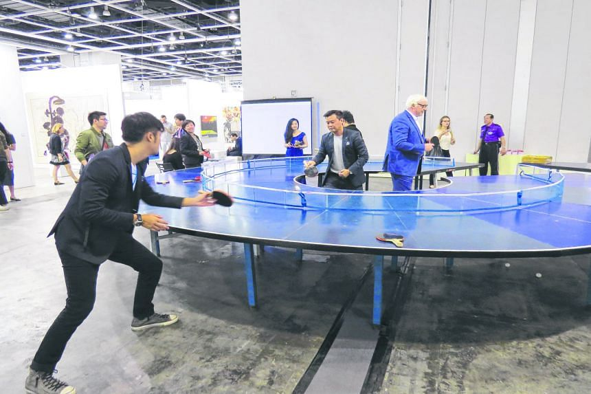 Visitors enjoying a game on Singapore contemporary artist Lee Wen's Ping-Pong Go Round table at the Art Basel show in Hong Kong last year.
