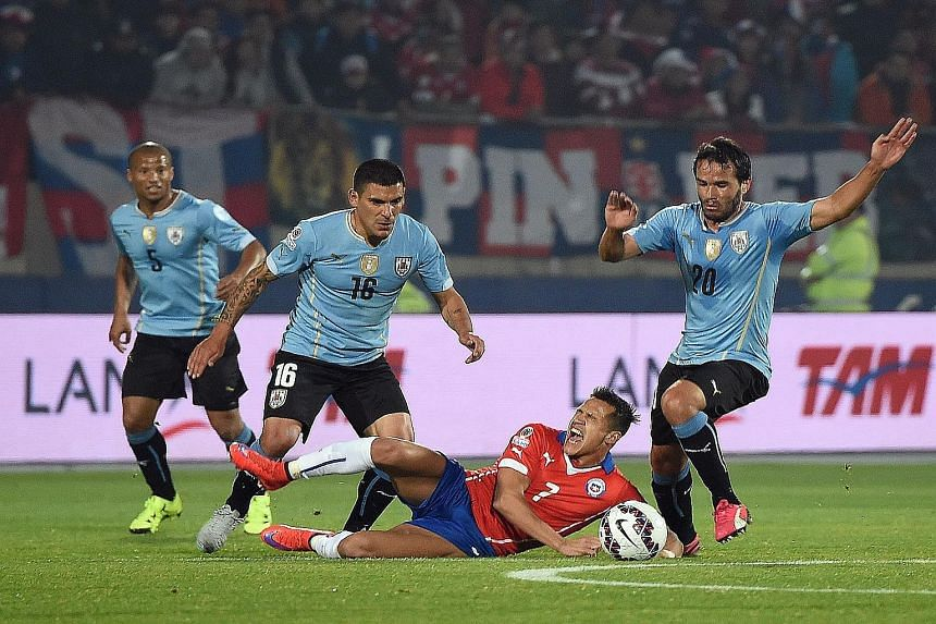 (Above) Copa holders Uruguay suffered a setback when Edinson Cavani, who flicked a hand into Gonzalo Jara's face, was sent off. (Left) It was a bruising match for Chile and Arsenal star Alexis Sanchez (on the ground), who bore the brunt of some tough
