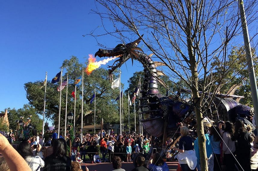 A fire-breathing dragon during a procession along a street in Disney World.
