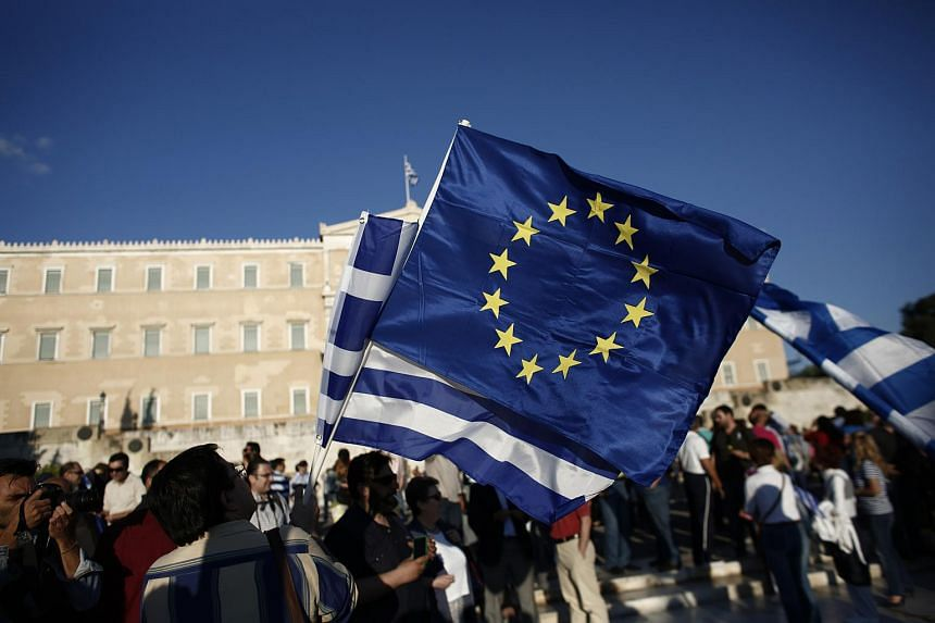 A protester holding a Greek and a European Union flag during a pro-EU demonstration in Athens.