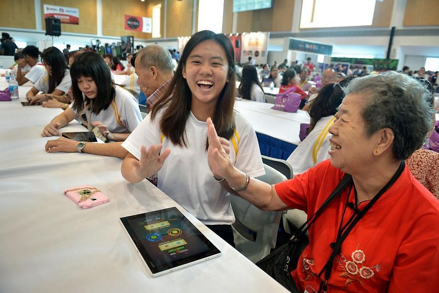 ITE College Central student Celine Si, 19, playing Fruit Ninja on a tablet with Madam Ng Geok Heok, 70 a resident of Thye Hwa Kwan Senior Activity Centre.