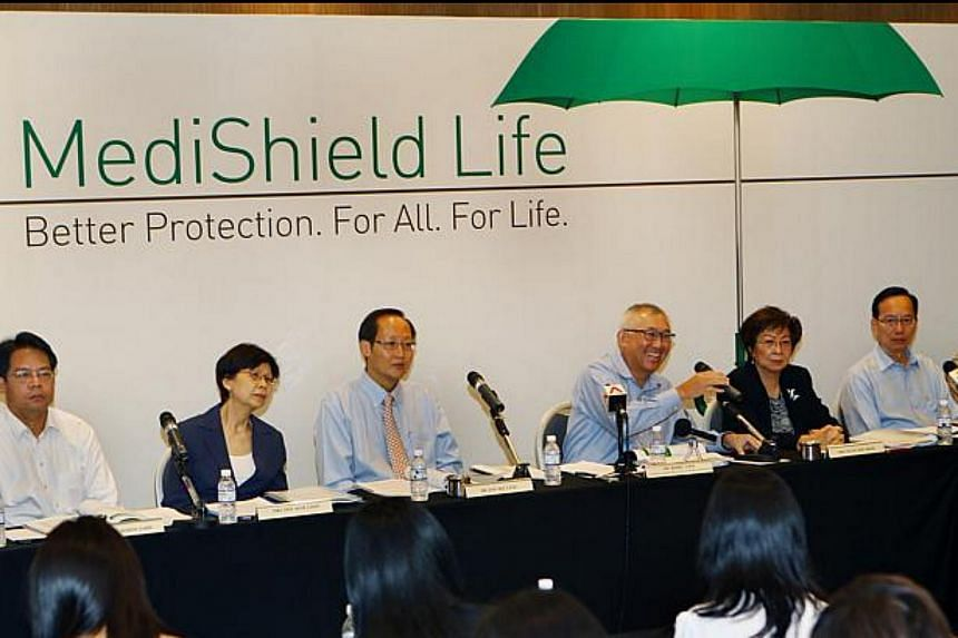 Chairman Mr Bobby Chin (fourth from left) with members of the Medishield Life Review Committee, speaking during the press conference, held at the Suntec City Convention Centre on June 24, 2014.