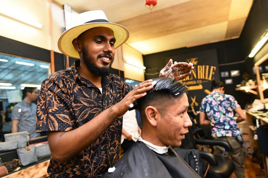 Barber Siva Guru, 21, applying mousse on a customer at The Golden Rule Barber Co. at Geylang Serai bazaar. -- PHOTO: LIM YAOHUI FOR THE STRAITS TIMES