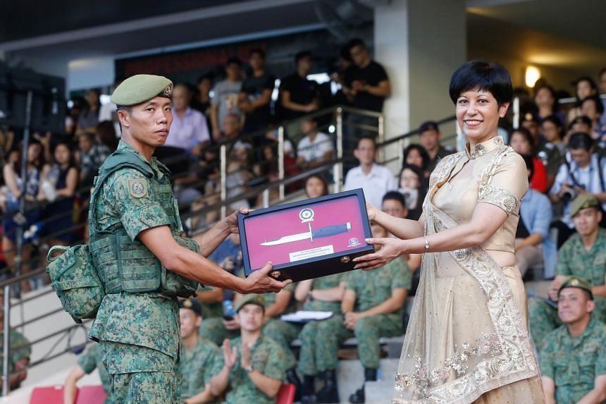 Specialist Cadet Yong Heng Soon receiving the Golden Bayonet, which is awarded to the top 10 per cent of trainees, from Senior Minister of State Indranee Rajah yesterday.