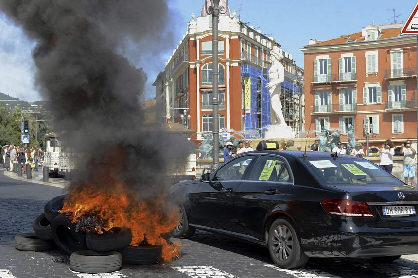 A striking taxi driving past burning tyres during a national protest against car-sharing service Uber in Nice, France, on June 25, 2015.