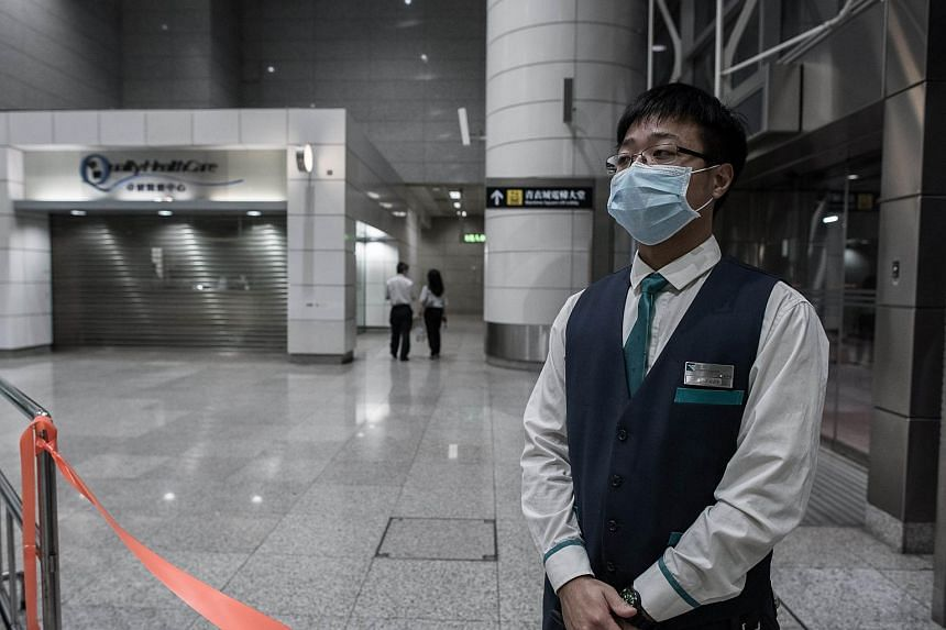 An MTR employee stands by a restricted area next to a closed clinic (L) at the Tsing Yi MTR station in Hong Kong on June 10, 2015.