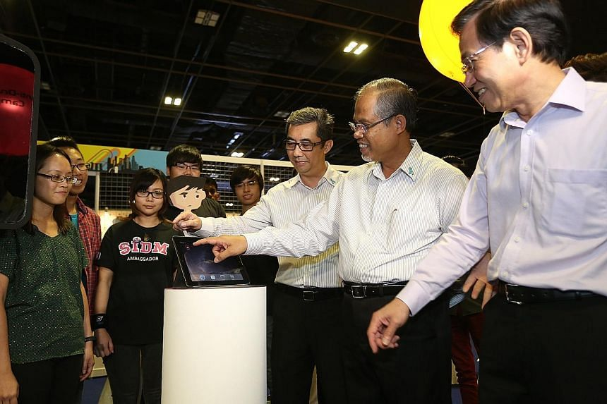 (From right) Mr Chan Lee Mun, principal and chief executive officer of Nanyang Polytechnic, Mr Masagos and Mr Ng Ser Song, director of Central Narcotics Bureau, checking out the mobile game application Nelzon.