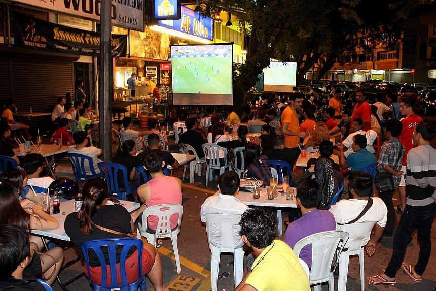 Football fans watching a televised match at an eatery in Kuala Lumpur. A minister has said that the proposal to end operating hours at midnight follows complaints about 24-hour restaurants and hawker centres.