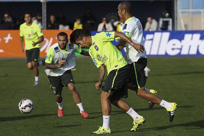 Brazil's Liverpool-bound forward Roberto Firmino losing the ball under the challenge of his team-mate during their training session on Wednesday.