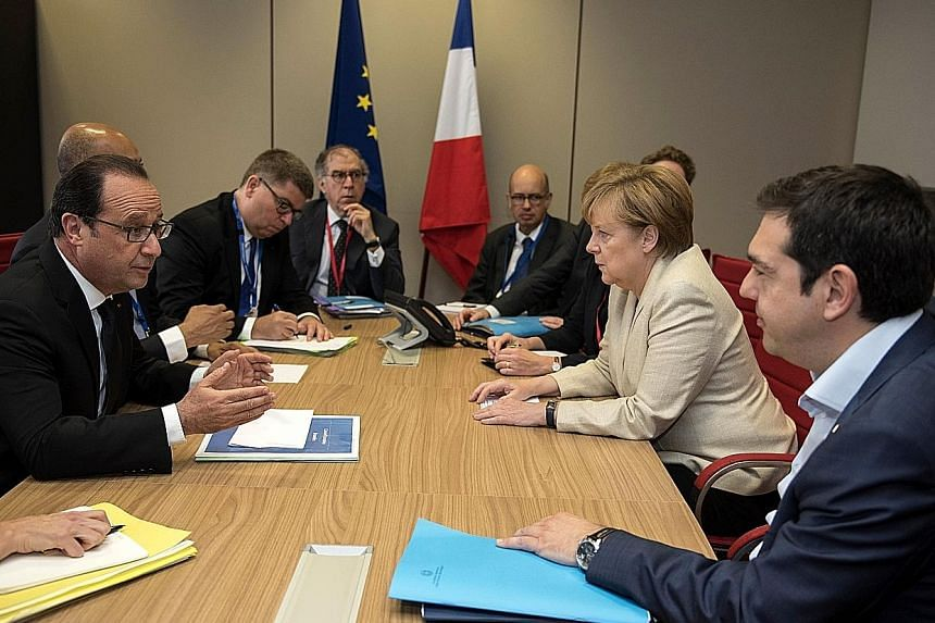 Mr Francois Hollande (left) in talks with Dr Angela Merkel (second from right) and Mr Alexis Tsipras (right) during a Brussels summit yesterday. Mr Hollande and Dr Merkel said today's emergency meeting of euro-zone finance ministers would be decisive