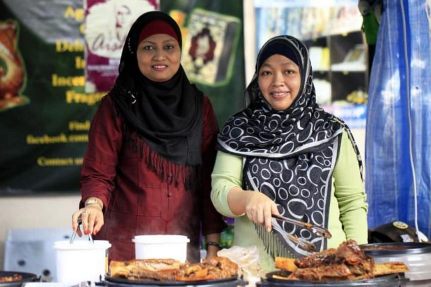 Ms Rosinar Latip (right), owner of the T Bob eatery, at T Bob's Honey BBQ Ribs with one of her stall assistants.