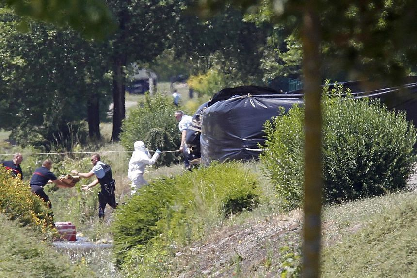 French crime scene investigators, Gendarmes and rescue forces are working next to a black plastic sheet outside a gas company site at the industrial area of near Lyon, France.