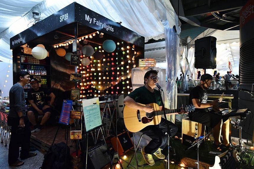 Singer-guitarist Muhammad Nurasyraf Sahri, 26, and drummer Hosni Fareed Altway, 32, from Attention! The New Portsdown, performing at the Geylang Serai bazaar.