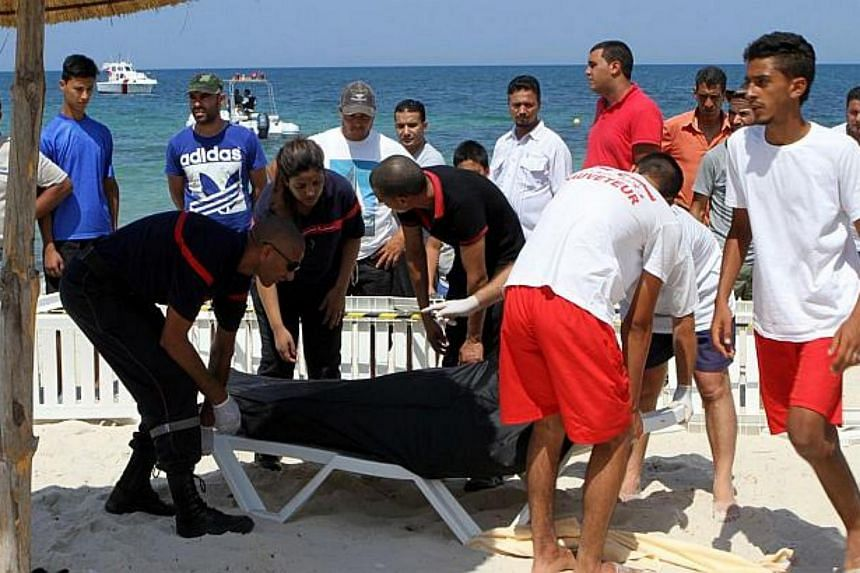 Tunisian lifeguards and medics transporting a covered body in the resort town of Sousse.