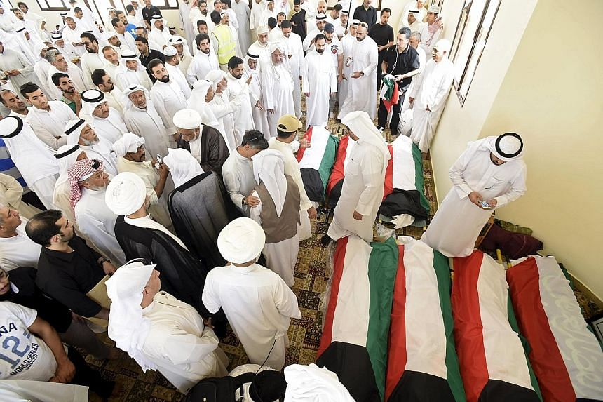 Kuwaiti flags are draped over the bodies of victims of last Friday's bombing, which killed 27 and injured at least 200 people.