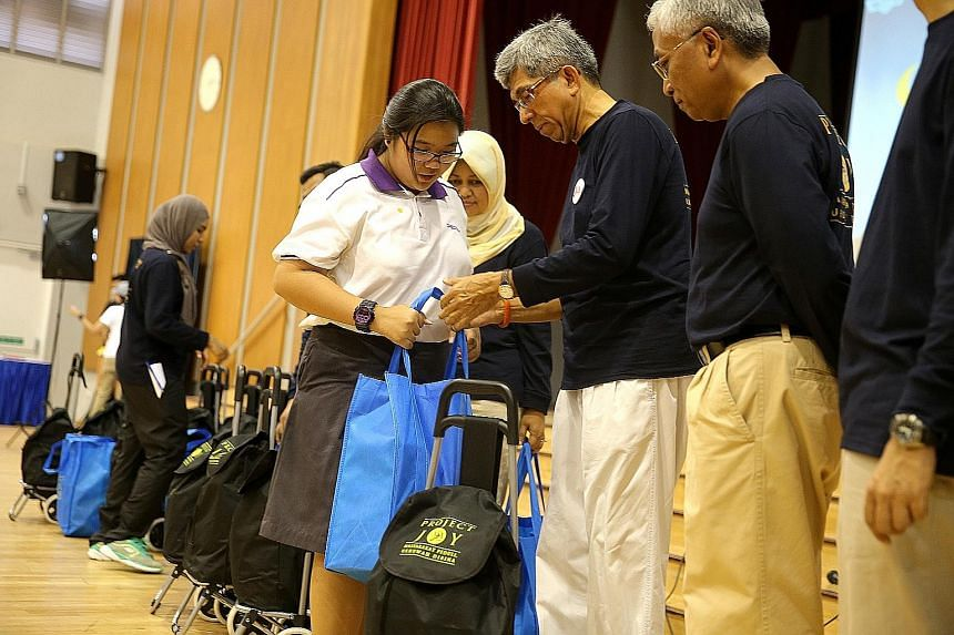 ABOVE: A Spectra Secondary School student from a low-income family receiving a bag of groceries from Minister-in- charge of Muslim Affairs Yaacob Ibrahim, as Senior Parliamentary Secretary for Education and Manpower Hawazi Daipi looks on. LEFT: Assoc