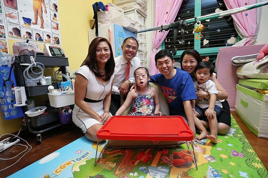 Six-year-old Chloe and her brother Cayden with their parents Kenneth and Patricia Mah. With them are the family's financial services consultants from AIA - Mr Tommy Tay and Ms Elaine Yeo (both on the left).