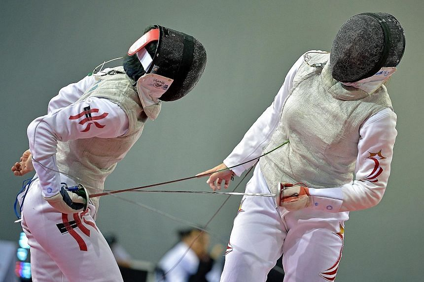 Singapore's Wang Wenying (right) losing a point to Hong Kong's Lin Po Heung during their last-16 encounter in the women's foil yesterday.