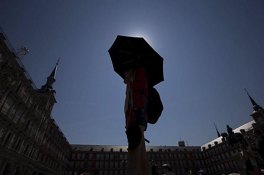 A tourist in Madrid's landmark Plaza Mayor in Spain on Friday. The forecast heatwave has prompted concern about increased pollution risks and strains on healthcare.