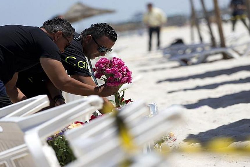 Men lay flowers at the site of the shooting attack.
