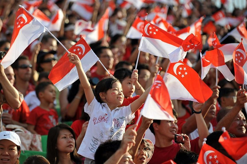 Spectators at the Padang decked out in the national colours of red and white and waving the national flag during the National Day Parade in 2010.