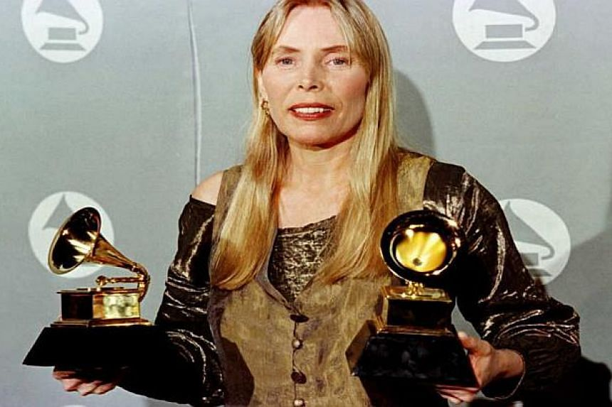 A 1996 file photo shows US singer Joni Mitchell holding two Grammy Awards.