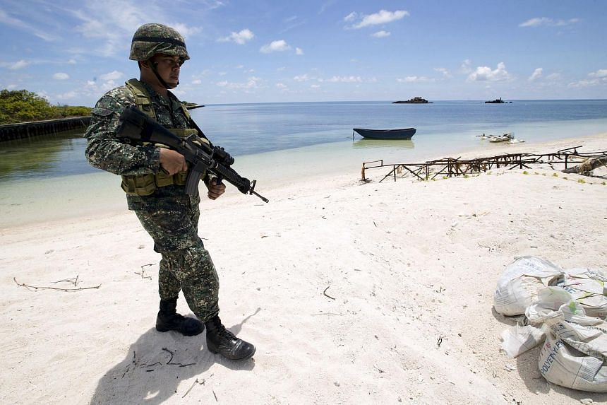 A Filipino soldier patrols the shore of Pagasa island (Thitu Island) in the Spratly group of islands in the South China Sea, west of Palawan, Philippines, in this May 11, 2015 file photo.