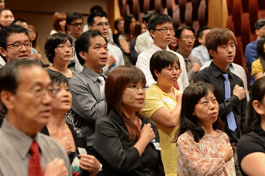 New citizens reciting the Singapore pledge after receiving their pink identity cards at the Asian Civilisations Museum in this file photo taken in 2013. PHOTO: ST FILE
