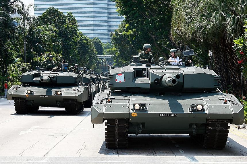 Reporter Lim Yi Han (in white in right tank) talking to tank commander Jon Lee aboard the Leopard 2SG Main Battle Tank. The column had stopped on Nicoll Highway to wait for the go-ahead while en route to the Padang.