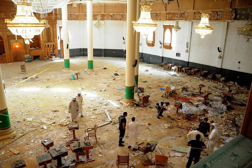 Medics and security forces gather inside Imam Sadiq Mosque following a suicide bombing in al-Sawaber, Kuwait City, Kuwait, 26 June.