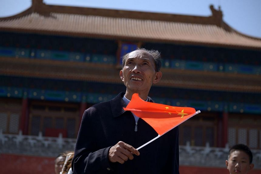A man holding a Chinese national flag at the Forbidden City in Beijing.