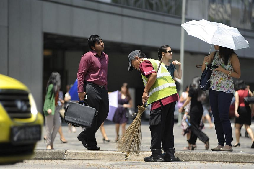 A cleaner sweeping the road outside Raffles City.