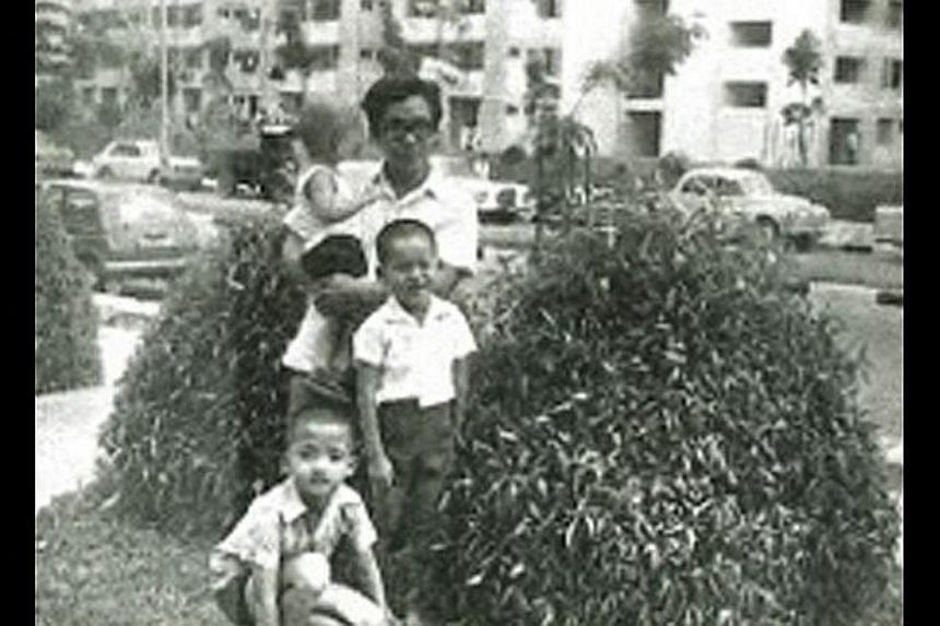 Barry Yeow as a child (standing) with his older brother Jerry (in front) and younger brother Terry in their father Thomas' arms.