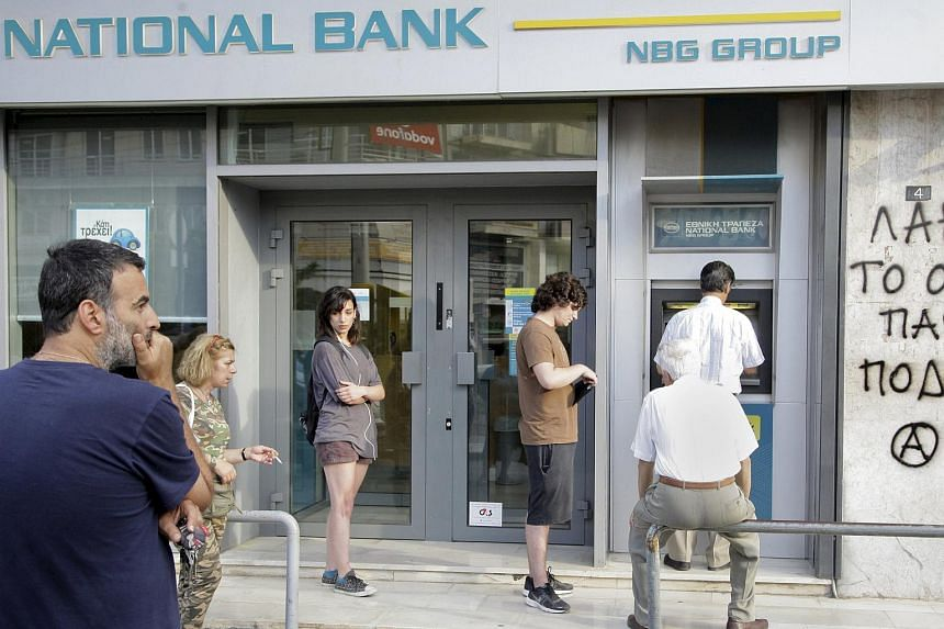 People line up to withdraw cash from an ATM outside a National Bank branch in Iraklio on the island of Crete, Greece, on June 28, 2015.
