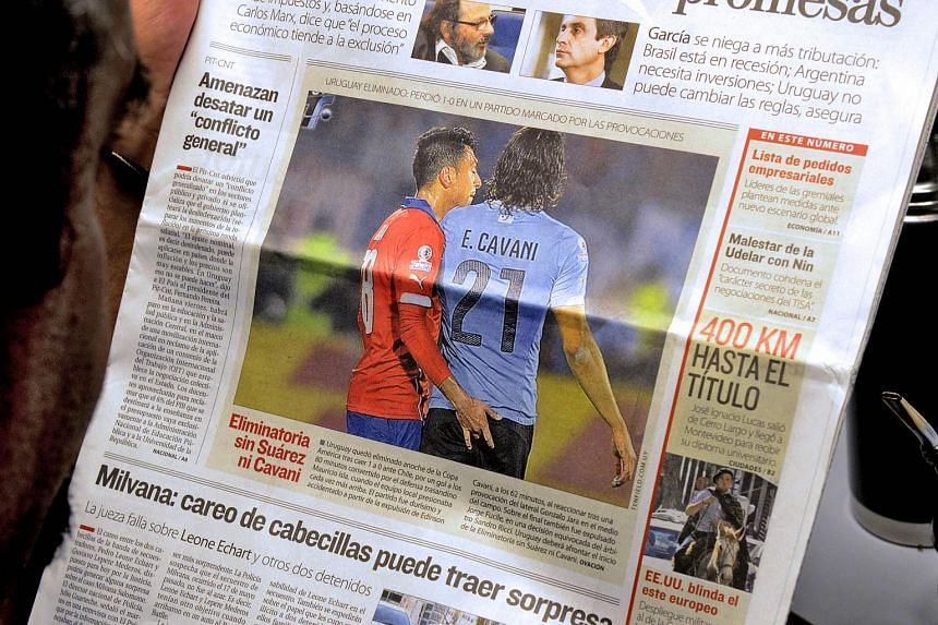The front page of an Uruguayan newspaper shows on June 25, 2015, a picture of Chile's football team defender Gonzalo Jara (left) provoking Uruguay's Edinson Cavani during their Copa America 2015 quarter-finals football match in Santiago.