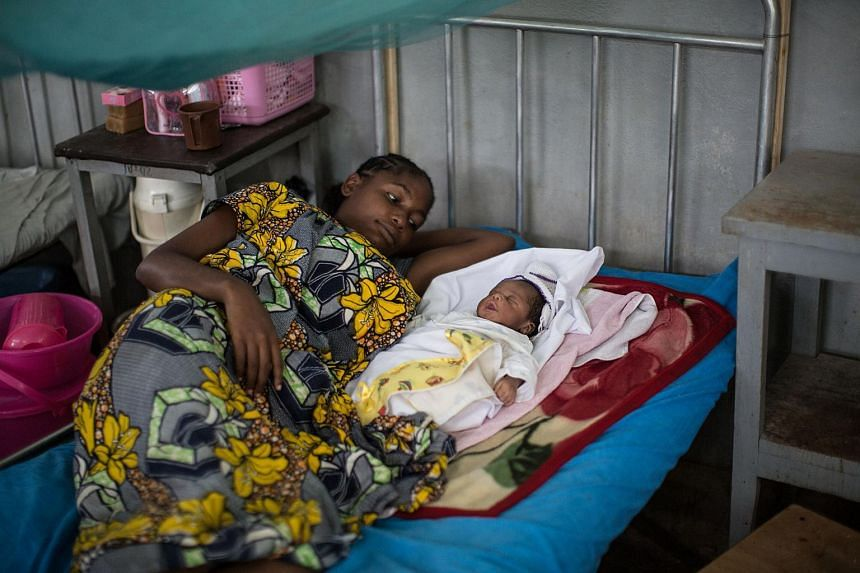 A woman lies next to her newborn baby at Zongo Hospital in Zongo, a small village in Congo.