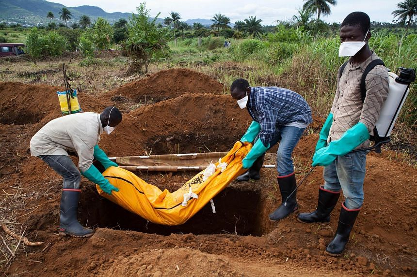 Volunteers in protective suits burying the body of a person who died from Ebola in Waterloo, Freetown.