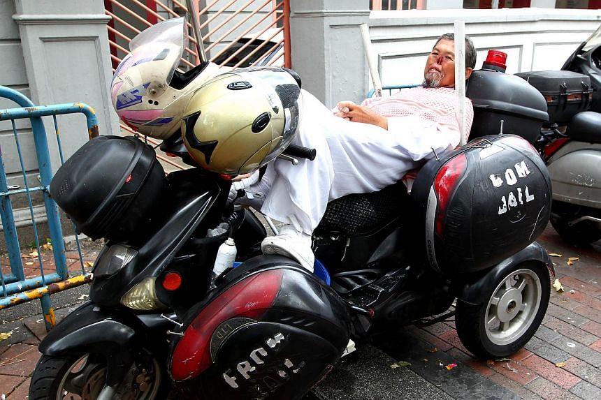 Mr Zheng sleeps on his bike at night.